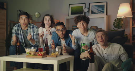 Happy friends doing high-five and clinking bottles watching sports on TV at home Footage