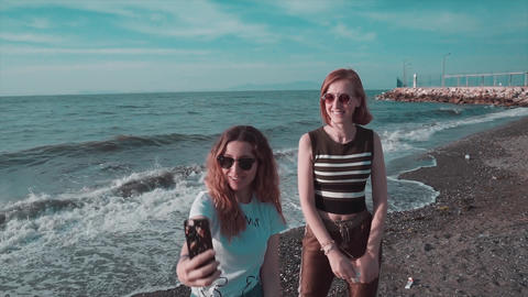 Two fashionable girl are close friend and taking selfie on seaside. Empty beach and clear sea, woman Live Action