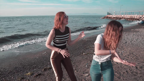 Girls are dancing on beach. Happy summer party, fun at beach. Friendship celebration Live Action