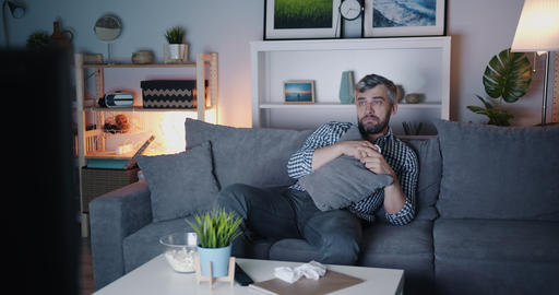 Bearded man watching TV eating popcorn and wiping nose with tissue Filmmaterial