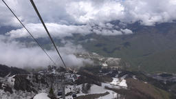 View from cable car ride down over high mountain peaks and canyon Footage