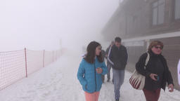 Sleepy tourists slowly walk through dense foggy path, alpine ski resort Footage