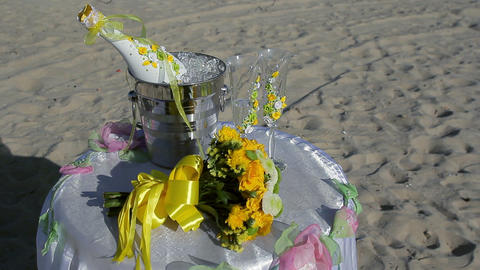 Champagne bottle in ice bucket, two glasses and wedding decor on the beach Footage