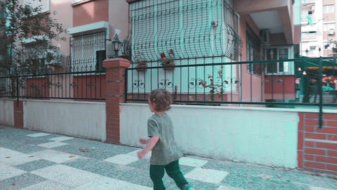 Children boy is playing run game on urban, street. Cute funny kid is joying between buildings. Footage
