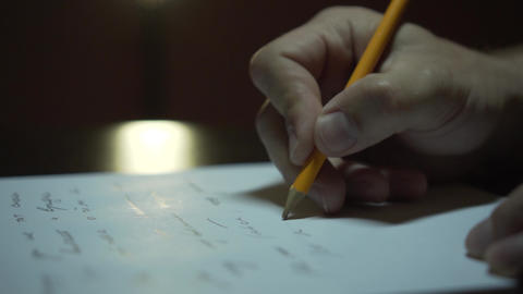 Male hand writing on a paper in the room. Close up of a male hand writing on Live Action