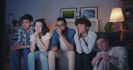 Multiracial group of young people watching TV at home at night yawning Filmmaterial