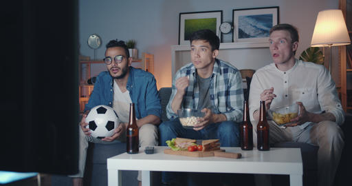 Handsome guys watching football game on TV eating snacks celebrating victory Footage