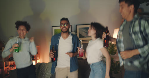 Joyful friends dancing clinking bottles laughing at home at night Filmmaterial