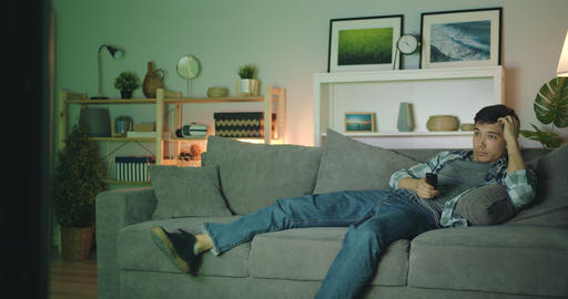 Handsome brunet watching TV at home using remote control relaxing on couch Filmmaterial