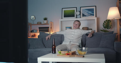 Joyful man watching TV at home laughing on couch at night enjoying comedy alone Filmmaterial