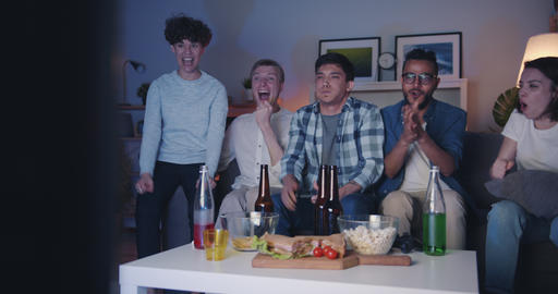 Joyful friends playing video game celebrating victory at night in apartment Filmmaterial