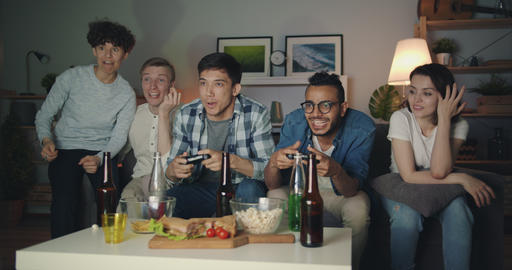 Multiethnic group of friends playing video game at home late at night having fun Filmmaterial