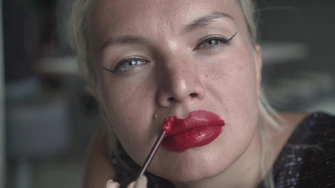 Seductive blonde woman, carelessly putting on red lipstick. Sexy blonde unevenly Footage