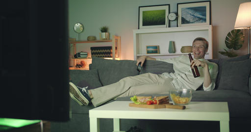 Cheerful guy watching TV drinking beer laughing at night in apartment Filmmaterial