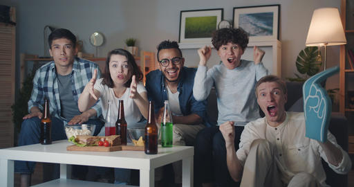 Slow motion portrait of excited students watching sports game on TV at night Filmmaterial