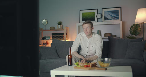 Bored guy clicking remote control looking for interesting program on TV at night Filmmaterial