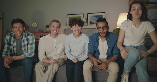 Multiethnic group of students watching TV at night laughing pointing at camera Filmmaterial