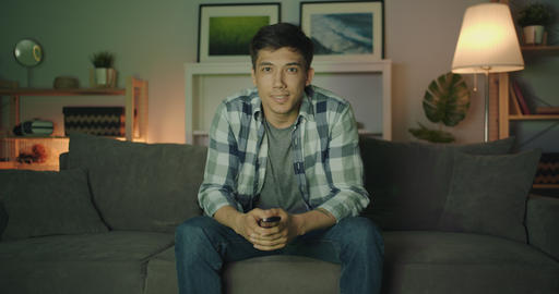 Portrait of mixed race young man watching TV at night laughing having fun Filmmaterial