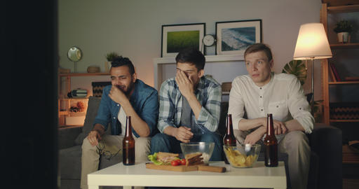 Unhappy young men with sad faces crying watching TV at night in apartment Filmmaterial
