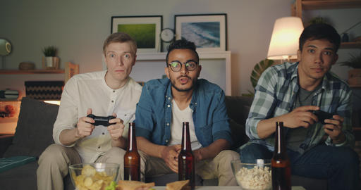 Handsome guys enjoying video game at home doing high-five having fun at night Filmmaterial