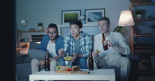 Guys watching scary movie on TV at night eating snacks drinking beer Filmmaterial