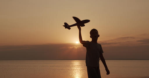 Happy child runs with a toy airplane on a sunset background. Childhood dreams Footage