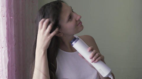 The girl dries her hair with a hairdryer. A young girl without makeup dries her Live Action