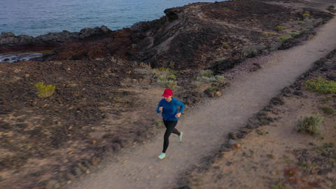Aerial view of woman runnning along the nature reserve at sunrise. Healthy Footage