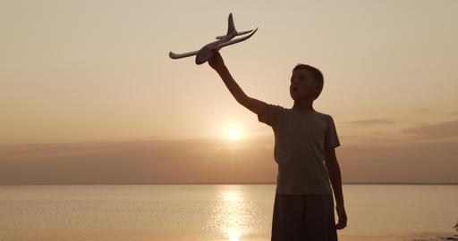 Happy kid playing with toy airplane against orange sun summer. Best childhood Footage