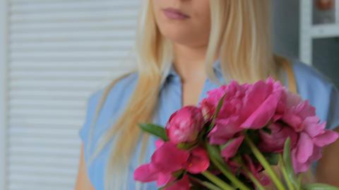 Florist woman making bunch at flower shop GIF