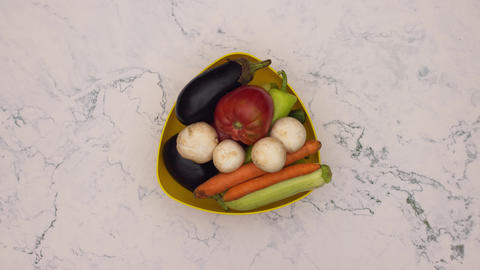 Stop motion animation of yellow dish filling with fresh and organic vegetables Animation