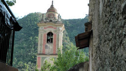 Europe Italy Liguria Airole village 020 baroque church tower at end of alley Footage