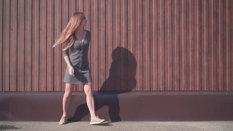Cute young girl walks in an urban environment. Happy girl in a dress near a Live Action
