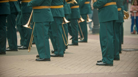 A wind instrument military parade - people in green costumes marching on the Live Action
