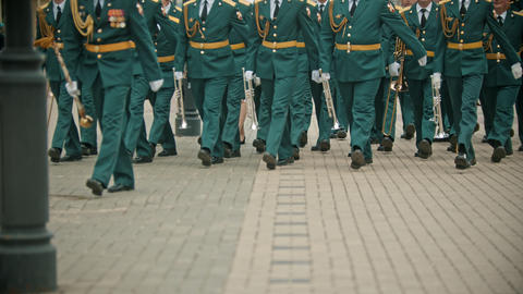 A wind instrument military parade - people in green costumes walking on the Live Action