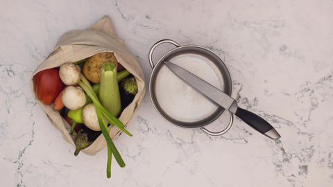 Stop motion animation of shopping bag full with vegetables and cookware appear on kitchen table Animation