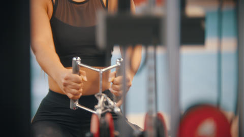 A sportive woman in sports clothes training in the gym - pulling the handles Footage