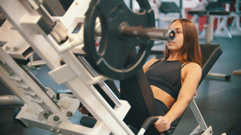 An athlete woman training in the gym - performing a leg press on the training Live Action