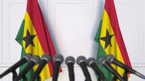 Ghanaian official press conference. Flags of Ghana and microphones. Conceptual Live Action