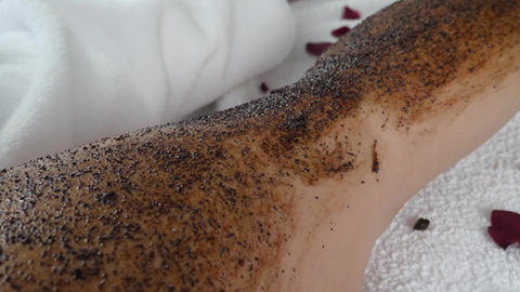 Female Masseur Hands Applies Coffee Scrub Mask on Woman's Leg Live Action