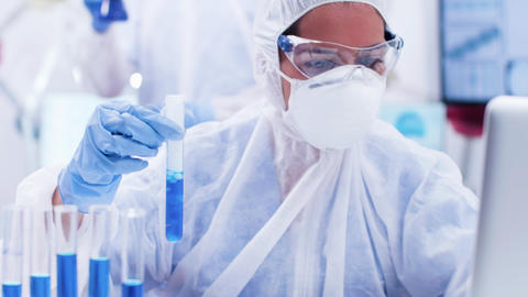 Female researcher in coverall equipment holding a test tube with smoking blue Footage