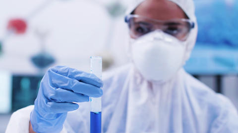 Woman scientist looking and holding a smoking blue fluid in a test tube Footage