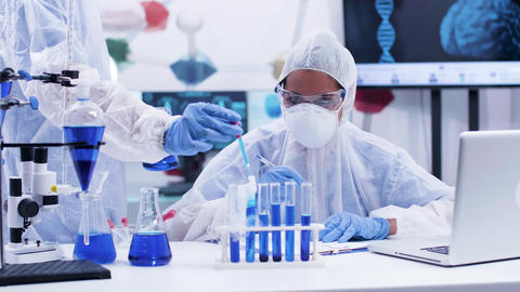 Woman scientist taking notes and looking at a smoking blue fluid in test tube Live Action