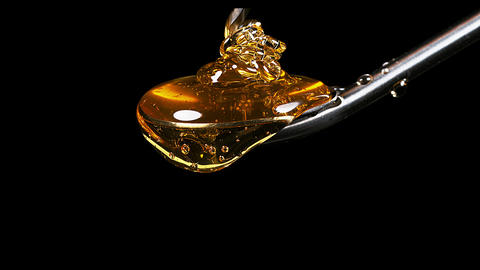 Honey Flowing from Spoon against Black Background, Real Time 4K Live Action