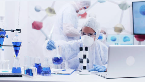 Woman scientist looking through microscope in laboratory wearing protection Footage