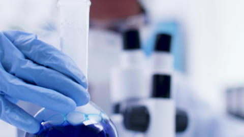 Close up of blue fluid in a bottle smoking in science laboratory Footage