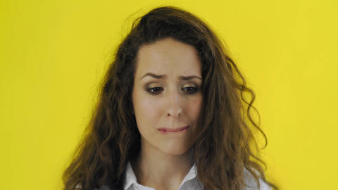 Upset young brunette woman portrait on yellow background. Young girl Live Action