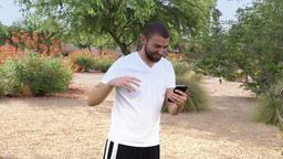 Young Male Millennial Plays Augmented Reality Game in Arizona Park Footage