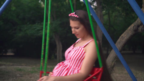 Pregnant girl in the park swinging on a swing. Happy girl with long dark hair in Footage