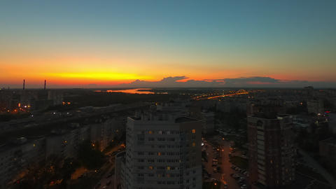 Modern city on evening sunset landscape. Time lapse orange sky over river Volga and evening city. Live Action